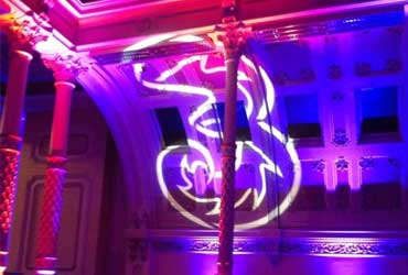 The Three logo projected onto the ceiling of a theatre at a brand activation event put together by event management company, Davis Events Agency, with purple, pink and blue light surrounding the logo.