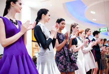 Women in cocktail dresses standing in a row and clapping at a corporate event organised by event management company, Davis Events Agency
